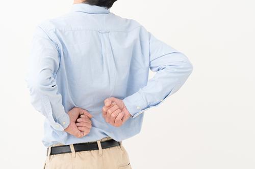 男性が腰を押さえている写真
