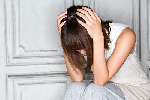頭を抱える女性のイメージ写真